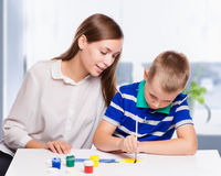 Young mother sitting at a table at home helping her small son Stock Photos