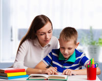 Young mother sitting at a table at home helping her small son with his homework from school as he writes notes in a notebook Stock Photo