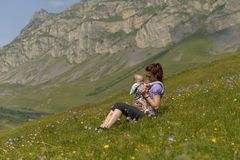 Young mother with a small child in a backpack-carrying travels in the mountains stock photography