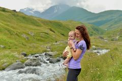 Young mother with a small child in a backpack-carrying travels in the mountains stock photo