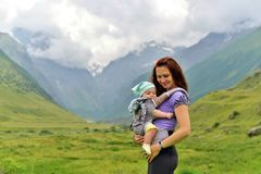 Young mother with a small child in a backpack-carrying travels in the mountains stock photos