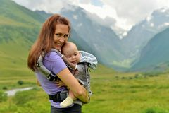 Young mother with a small child in a backpack-carrying travels in the mountains royalty free stock photography