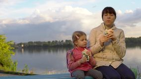 Mom and daughter together eat doner kebab in the street next to the pond.