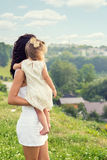 Young mother with a small daughter in his hands standing on the edge of the cliff and looks into the distance over the city Royalty Free Stock Photo