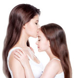 Young mother with a small daughter 8 years with long hair. Beautiful young mother with a small daughter 8 years with long hair at studio royalty free stock photos
