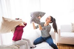 Young mother with a small girl at home having pillow fight. Young mother with a small girl at home, playing. A family having a pillow fight stock photos