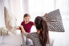 Young mother with a small girl at home having pillow fight. Young mother with a small girl at home, playing. A family having a pillow fight stock image