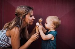 Young mother with small toddler girl outdoors in summer, eating ice cream. A young mother with small toddler girl outdoors in summer, eating ice cream royalty free stock photo