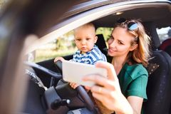 Young mother with smartphone and baby boy in the car. Young mother with her little son in the car. A women and baby boy pretending to be driving. Woman taking Royalty Free Stock Image
