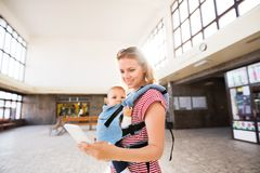 Young mother with smartphone and baby travelling. Royalty Free Stock Image