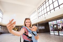 Young mother with smartphone and baby travelling. Royalty Free Stock Images