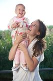 Young mother smiling outdoors with adorable baby Royalty Free Stock Photos