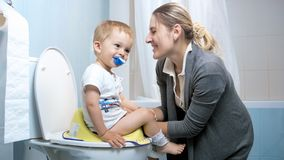 Young mother smiling to her toddler boy sitting on toilet. Mother smiling to her toddler boy sitting on toilet stock image