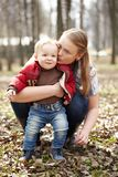 Young mother and son. Beautiful young mother kissing and embracing her one year sonny in the park. This shot was made in the first day of spring royalty free stock photography
