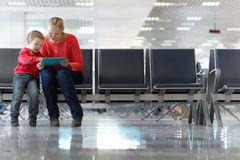 Young mother and son in an airport terminal. Sitting in the waiting room playing with a tablet computer as they wait for their flight Royalty Free Stock Images
