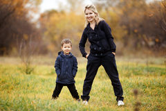 Young mother and son in autumn forest park, yellow foliage. Casual wear. Kid wearing blue jacket. Incomplete family. Young mother and son in autumn park in stock images