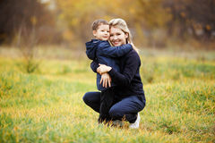 Young mother and son in autumn forest park, yellow foliage. Casual wear. Kid wearing blue jacket. Incomplete family Royalty Free Stock Image