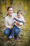 Young mother with son in autumn park Stock Photos