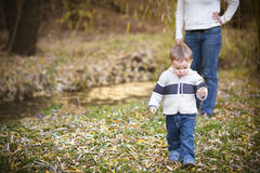 Young mother with son in autumn park Royalty Free Stock Photos