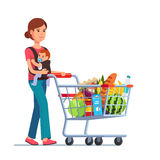Young mother with son baby toddler. In a sling pushing supermarket shopping cart full of groceries. Flat style vector illustration on white background stock illustration