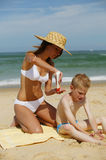 Young mother with son at the beach. Young mother with a straw hat applying sun cream on her son's back Stock Images