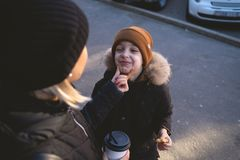 Young mother with son eat street food at winter time and have a fun stock image