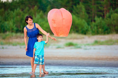 Young mother and son flying fire lantern together Stock Photo