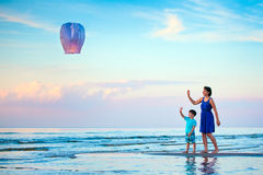 Young mother and son flying fire lantern together Royalty Free Stock Photo