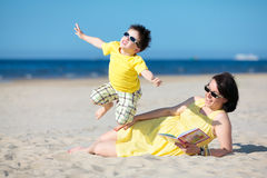 Young mother and son having fun on the beach Royalty Free Stock Images