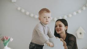 Young mother and son having fun with toy horse in slow motion indoor. Baby riding blue horse. Family concept in white t-shirts and jeans stock video footage