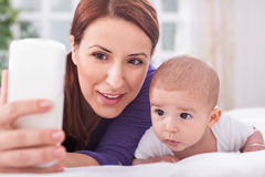 Young mother with son looking to the mobile phone Stock Photos
