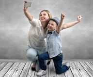 Young mother and son are photographed on a mobile phone ,making selfie .Stylish,trendy,modern royalty free stock photos