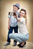 Young mother and son are photographed on a mobile phone ,making selfie .Stylish,trendy,modern Stock Photos