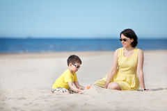 Young mother and son playing on sand beach Stock Images