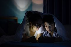 Young mother with son playing with a smartphone on a bed. Asian family young mother with son are playing with a cellphone or smartphone on a bed. night royalty free stock photos