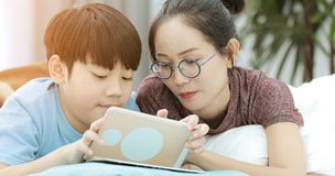 Young mother with son playing with a smartphone on a bed. royalty free stock photo