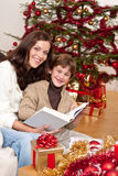 Young mother with son reading book on Christmas Stock Photography