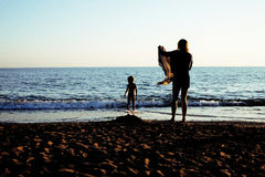 Young mother with son resting on sea coast, happy family togethe Stock Photo
