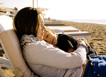 Young mother with son resting on sea coast, happy family togethe Royalty Free Stock Image