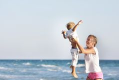 Young mother and son on sea background Stock Images