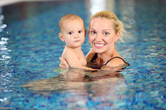 Young mother and son in swimming pool. Portrait of young cheerful mother and little son in swimming pool Stock Photo