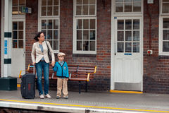 Young mother and son waiting for train on railway station Royalty Free Stock Images