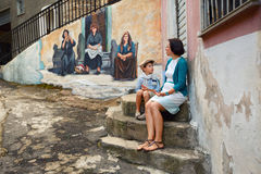 Young mother and son walking outdoors in city. Young mother and son walking outdoors in village ORGOSOLO, ITALY. Murals wall paintings about political and Stock Image