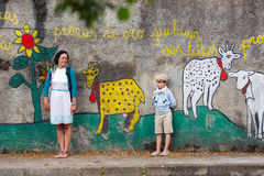 Young mother and son walking outdoors in city. Young mother and son walking outdoors in village ORGOSOLO, ITALY. Murals wall paintings about political and Stock Photos
