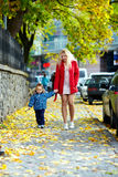 Young mother and son walking urban city street Stock Photo