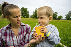 Young mother and son 1.3 years on  green lawn .Boy drinking milk . Stock Images