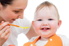 Young mother spoon-feeding happy baby girl Royalty Free Stock Photo