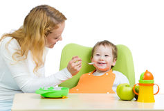 Young mother spoon feeding her baby boy Royalty Free Stock Images