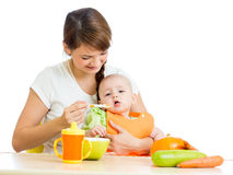 Young mother spoon feeding her baby girl Stock Photos