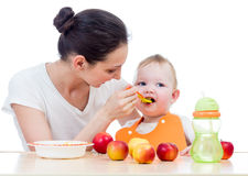 Young mother spoon feeding her baby girl Royalty Free Stock Photography